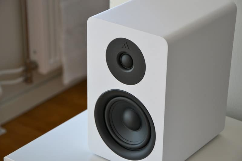 A microwave oven sitting on top of a speaker