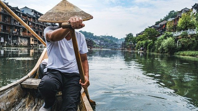 A man sitting in a boat on a body of water